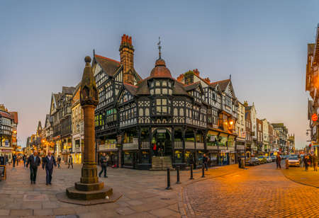 CHESTER, UNITED KINGDOM, APRIL 7, 2017: Sunset view of traditional tudor houses alongside the Bridge street in the central Chester, England 新闻类图片