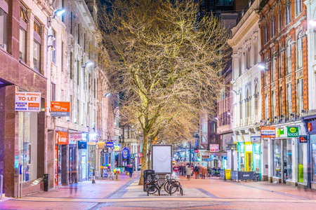 BIRMINGHAM, UNITED KINGDOM, APRIL 8, 2017: People are walking on a street in Birmingham during night, England