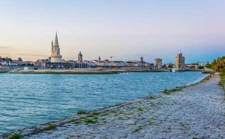 Sunset view of Port of La rochelle guarded by tour de la lanterne, tour de la chaine and tour Saint Nicholas, France