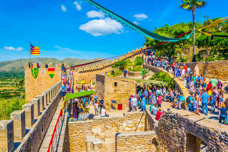 CAPDEPERA, SPAIN, MAY 21, 2017: People are strolling thorugh Capdepera castle during a medieval market, Mallorca, Spain