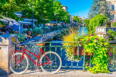 L'ISLE-SUR-LA-SORGUE, Francia, 24 de junio de 2017: Bicicleta bloqueada en una barandilla en el centro histórico de l'Isle sur la Sorgue en Francia Editorial