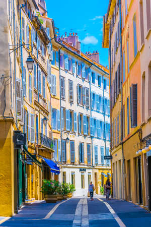 AIX-EN-PROVENCE, FRANCE, JUNE 18, 2017: People are strolling through a narrow street in the center of Aix-en-Provence, France