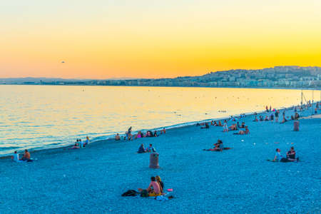 NICE, FRANCE, JUNE 11, 2017: Sunset view of people on a beach in Nice, France 新聞圖片