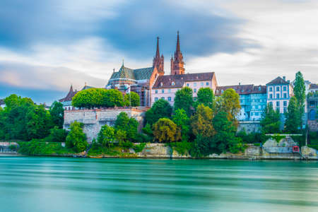 Sunset view of riverside of Rhine in Basel dominated by majestic building of Munster church, Switzerland Stock Photo