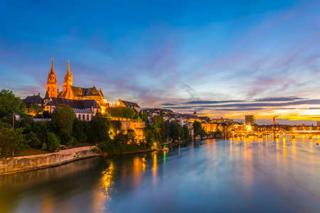 Sunset view of riverside of Rhine in Basel dominated by majestic building of Munster church, Switzerland Stok Fotoğraf