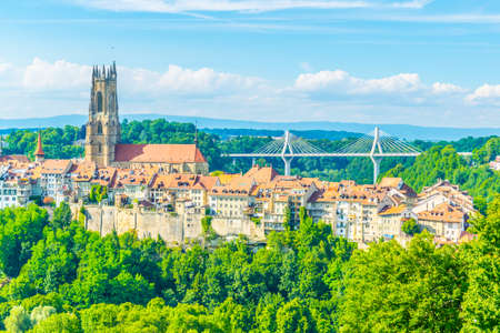 Tower of the cathedral of Saint Nicholas standing over skyline of Fribourg, Switzerland