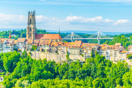 Tower of the cathedral of Saint Nicholas standing over skyline of Fribourg, Switzerland Stock Photo