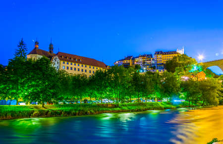 Night view of Pont de Zaehringen standing over valley of river Sarine in Fribourg, Switzerland 免版税图像