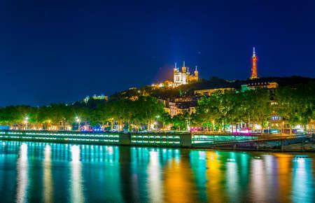 Illuminated Basilique Notre Dame de Fourvière viewed behind river Saone in Lyon, France 免版税图像