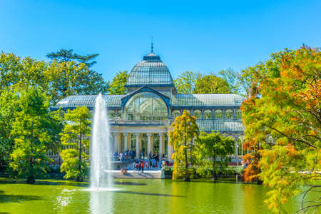Fountain in a pond in front of the crystal palace at the Parque del Buen Retiro in Madrid, Spain Editorial