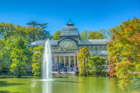 Fountain in a pond in front of the crystal palace at the Parque del Buen Retiro in Madrid, Spain