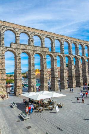 SEGOVIA, SPAIN, OCTOBER 4, 2017: People are walking towards famous aqueduct at Segovia, Spain 스톡 콘텐츠