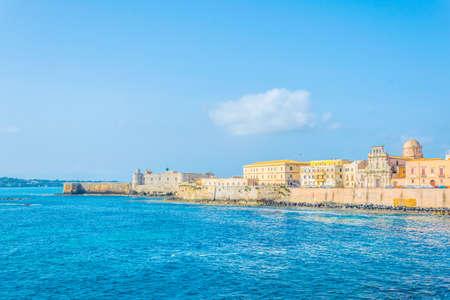 Blick auf die Strandpromenade rund um die Altstadt von Syrakus in Sizilien, dominiert von Chiesa dello Spirito Santo und Castello Maniace, Italien