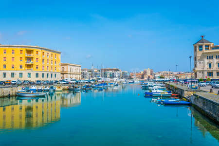 Boats are moored next to the old town of Syracuse, Sicily, Italy
