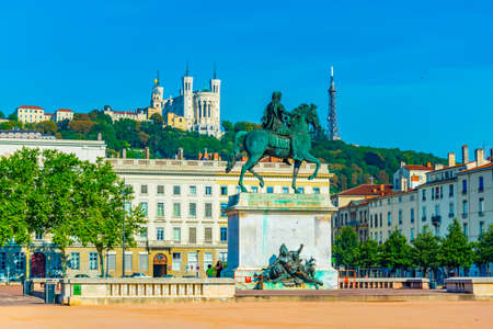 Basilica Notre-Dame de Fourviere viewed behind statue of Louis XIV in Lyon, France
