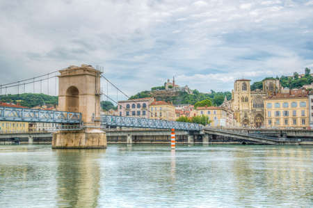 Cathedral in Vienne viewed behind a pedestrian bridge over river Rhone, France