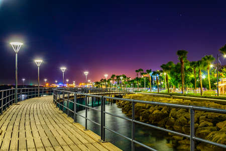Night view of Molos promenade with several piers leading to the mediterranean sea in Limassol, Cyprus