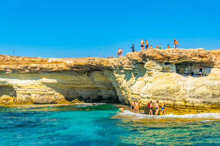 AGIA NAPA, CYPRUS, AUGUST 30, 2017: Tourists are jumping into the mediterranean sea from sea caves at cap greco in the south-eastern cyprus Reklamní fotografie - 121016867