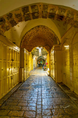 People are strolling among various shops situated in a narrow street in the old town of Jerusalem, Israel