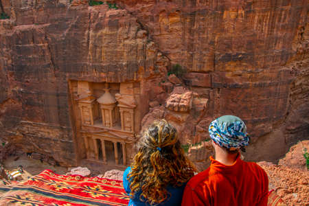 Young couple sitting at a viewpoint on Al Khazneh tomb also called Treasury at Petra, Jordan