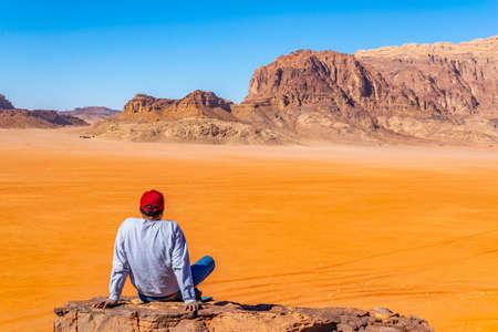 A lonely man is observing Wadi Rum desert in Jordan from a hilltop Foto de archivo