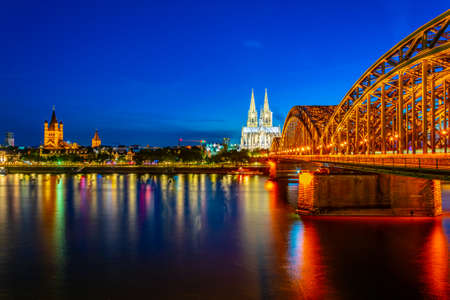Night view of cityscape of Cologne with Hohenzollern bridge, cathedral and Saint Martin church, Germany Фото со стока - 128287137