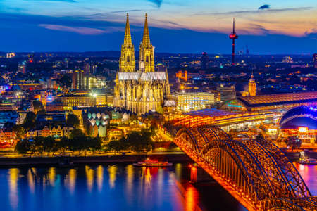Night aerial view of cityscape of Cologne with Hohenzollern bridge, cathedral and Saint Martin church, Germany Фото со стока - 128287350
