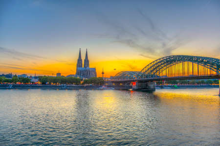 Sunset view of the cathedral in Cologne and Hohenzollern bridge over Rhein, Germany Фото со стока - 128287356