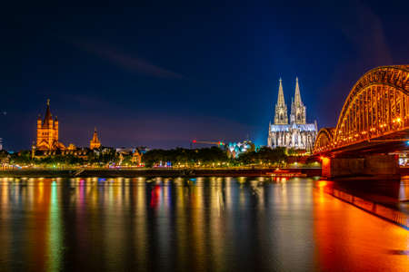 Night view of cityscape of Cologne with Hohenzollern bridge, cathedral and Saint Martin church, Germany