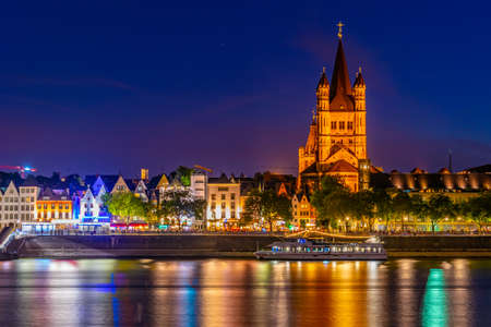 Night view of the riverside promenade and Saint Martin church in Cologne, Germany