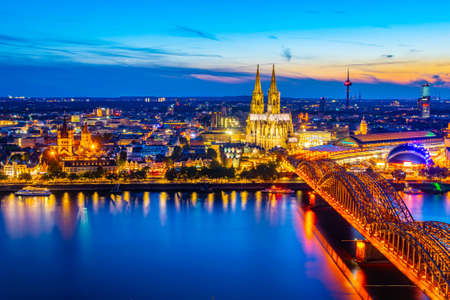 Night aerial view of cityscape of Cologne with Hohenzollern bridge, cathedral and Saint Martin church, Germany