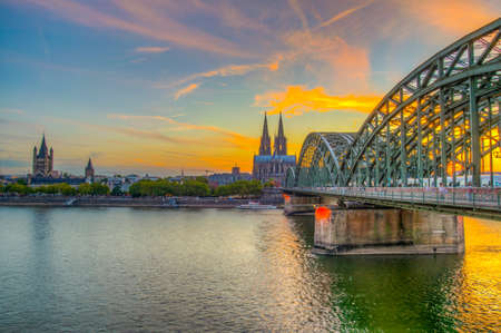 Sunset view of cityscape of Cologne with Hohenzollern bridge, cathedral and Saint Martin church, Germany Banque d'images - 129550017