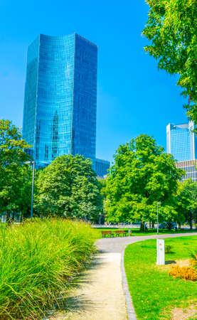 People are walking under Skyscrapers in Frankfurt in a small green garden, Germany