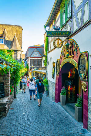 RUDESHEIM AM RHEIN, GERMANY, AUGUST 16, 2018: Tourists are strolling through famous Drosselgasse street in Rudesheim am Rhein in Germany Фото со стока - 122639991