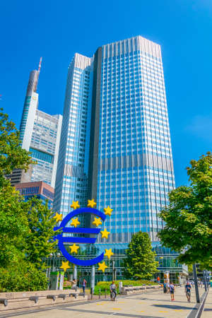 FRANKFURT, GERMANY, AUGUST 18, 2018: People are passing Euro sign in front of Eurotower in Frankfurt, Germany Редакционное