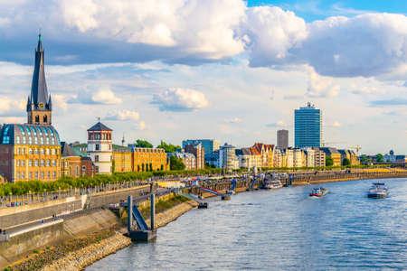 Düsseldorf, Niemcy, 10 sierpnia 2018: Ludzie spacerują nad brzegiem Renu w Dusseldorfie z kościołem Saint Lambertus, Niemcy Publikacyjne