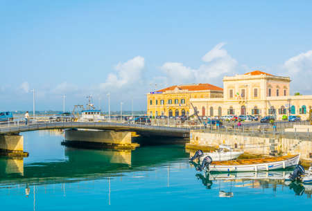 Boats are moored next to the old town of Syracuse, Sicily, Italy Редакционное