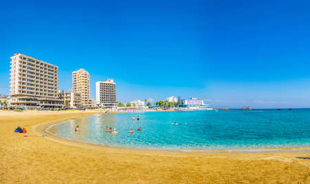 FAMAGUSTA, CYPRUS, AUGUST 29, 2017: People are enjoying a sunny day on a beach in front of Varosia district of Famagusta, Cyprus Редакционное