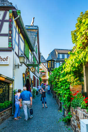 RUDESHEIM AM RHEIN, GERMANY, AUGUST 16, 2018: Tourists are strolling through famous Drosselgasse street in Rudesheim am Rhein in Germany