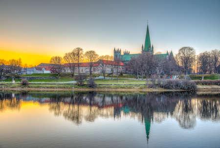 Sunset view of Nidaros cathedral reflecting on river Nidelva in Trondheim, Norway