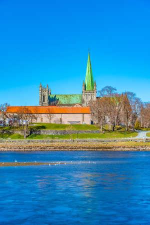 Nidaros cathedral reflecting on river Nidelva in Trondheim, Norway