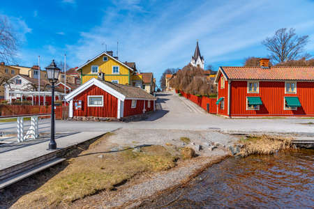 White church in Nora viewed behind timber houses, Sweden Stock Photo