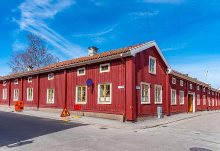 Holzhäuser neben einer schmalen Straße in Nora, Schweden