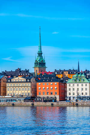 German church and colourful buildings of Gamla Stan in Stockholm viewed across the water, Sweden. Stock Photo