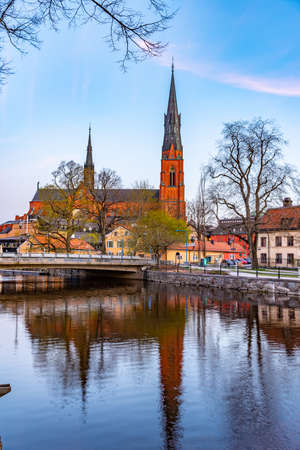 Sunset view of Uppsala cathedral reflecting on river Fyris in Sweden Stock Photo