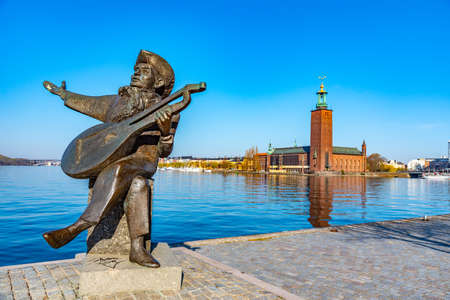 View of statue of Evert Taube with town hall of Stockholm in background, Sweden