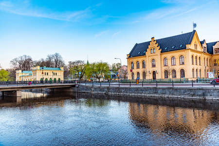 Sunset view of notable buildings alongside river Fyris in Uppsala, Sweden