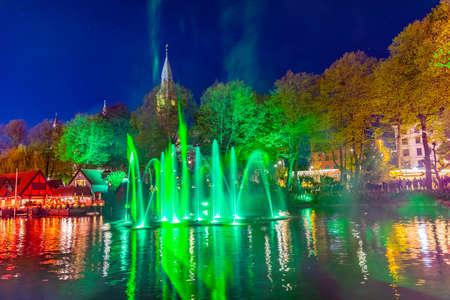 Light and sound show on surface of a pond at Tivoli gardens amusement park in Copenhagen, Denmark