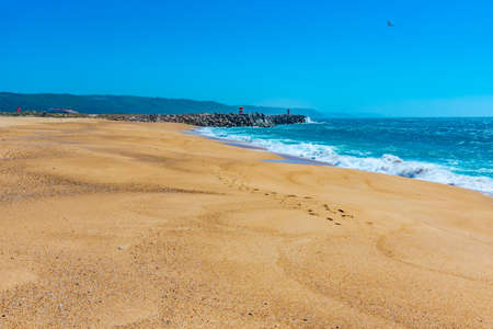 People are enjoying a sunny day on a beach in Nazare in Portugal