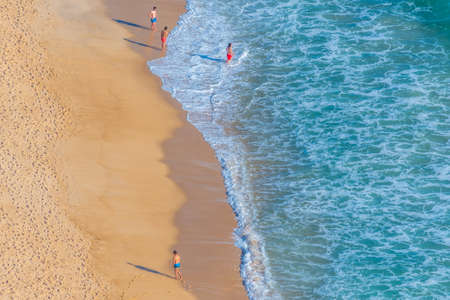 Aerial view of people enjoying a sunny day on a beach in Nazare in Portugal